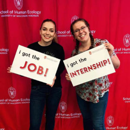 Two students smiling and holding signs that say, I got the Job! and I got the Internship!