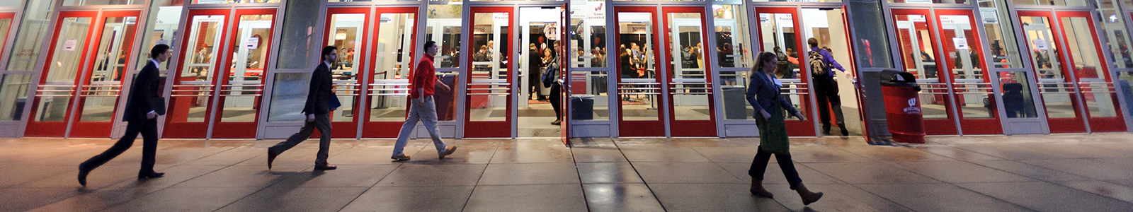 Outside Kohl Center during the Career and Internship Fair. students in professional attire walk in front of the building.