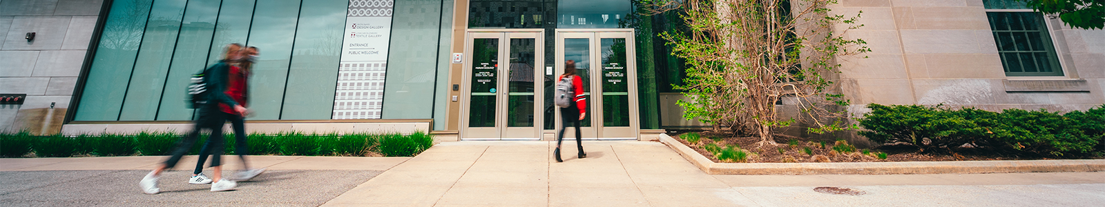 3 students wearing masks, walk through the front doors of Nancy Nicholas Hall.